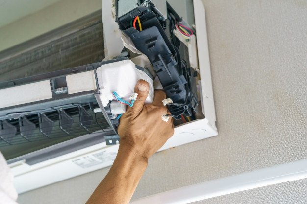 service-technician-is-cleaning-repair-maintenance-air-conditioner | handyman in dubai | Hnadyman services in dubai
